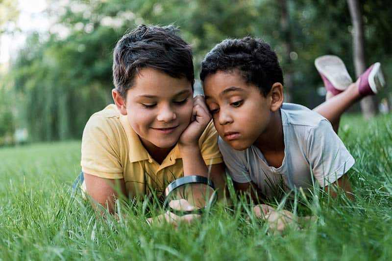 boys looking at grass with magnifying glass