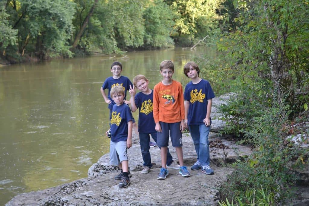 pramuka anak di luar ruangan dengan sungai kecil
