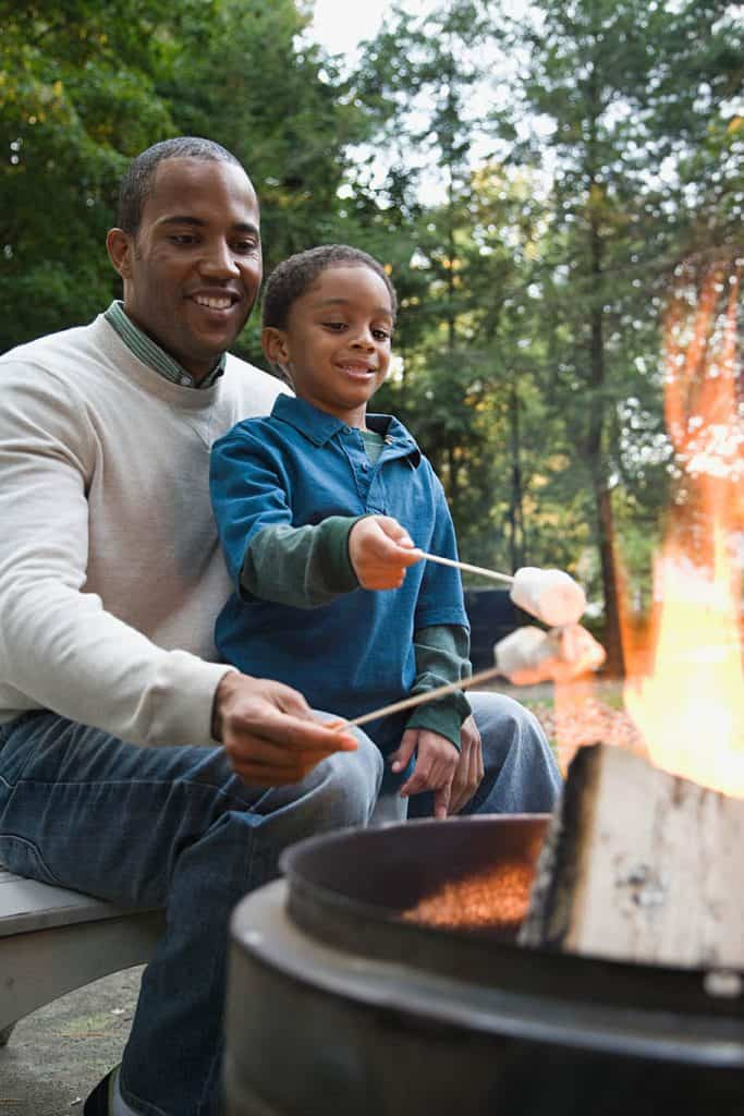 father helping son safely make s'mores