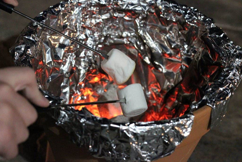 toasting marshmallows over terra cotta pot smore maker