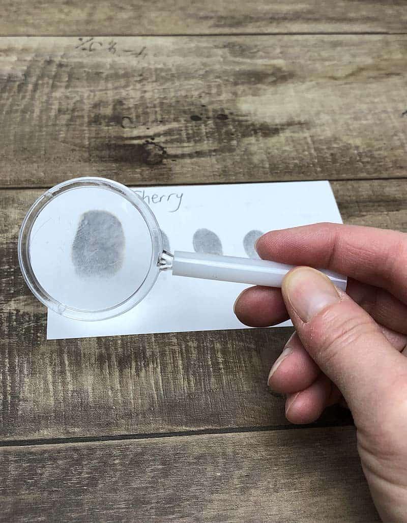memeriksa sidik jari dengan kaca pembesar