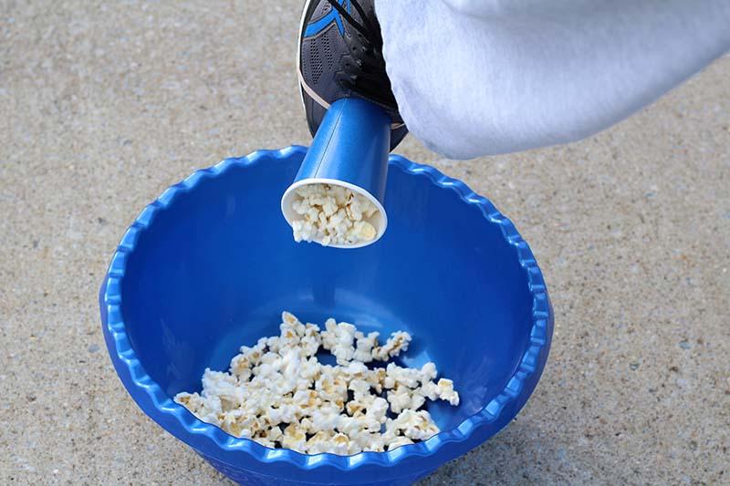 dumping popcorn in bowl